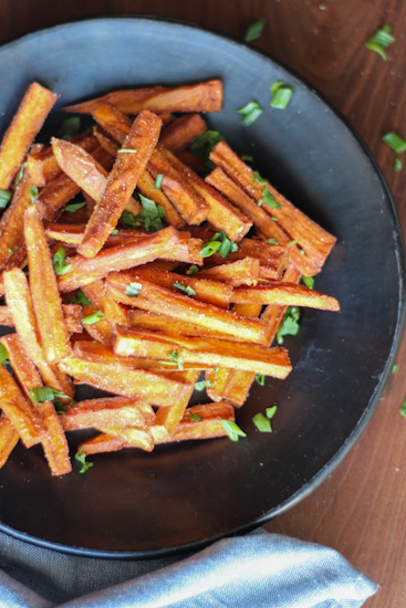 Fried sweet potato fries on a black plate, sprinkled with cilantro and green onion.