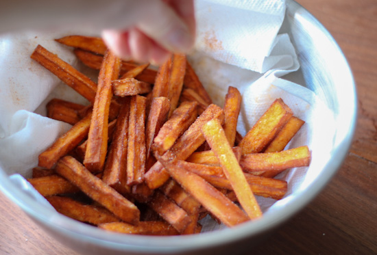 Sweet potato fries after they came out of the fryer, in a bowl lined with a paper towel, with someone seasoning them over top