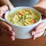 Two hands holding. Small white bowl of mulligatawny soup