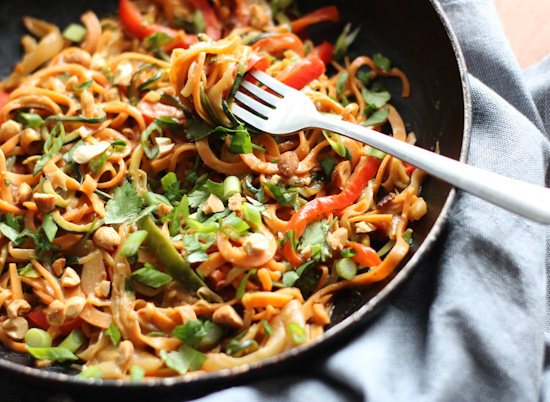 Sweet potato and zucchini noodles, peppers, and onions with spicy peanut sauce in a skillet with a fork