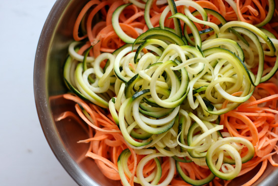 Spiralized sweet potato and zucchini in a stainless steel bowl