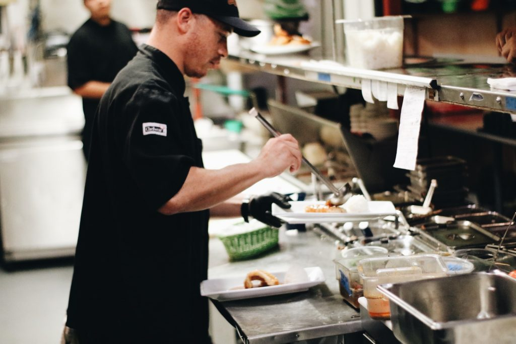 Chef Tony Duman seasoning a plate of food at the pass