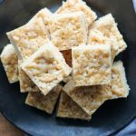 Golden Oreo Rice Krispie Treats with Salted Tahini Drizzle sliced and stacked on a black plate