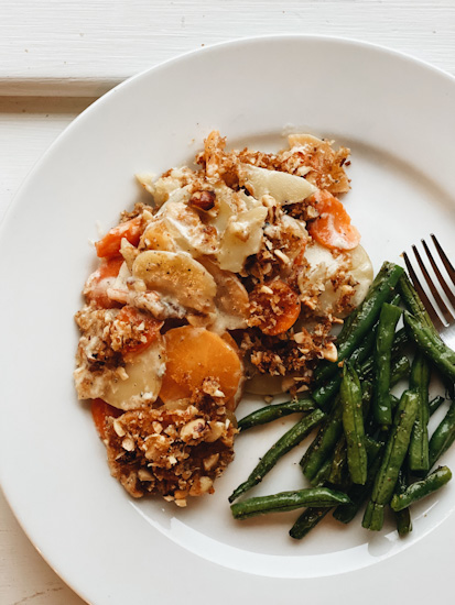 Hazelnut Root Vegetable Gratin served on a plate with green beans on the side