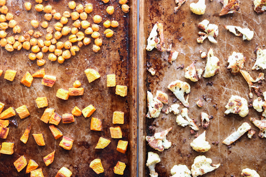 Roasted chickpeas, sweet potatoes, and cauliflower on baking sheets