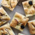 squares of Rosemary, Onion, and Olive Focaccia on parchment paper