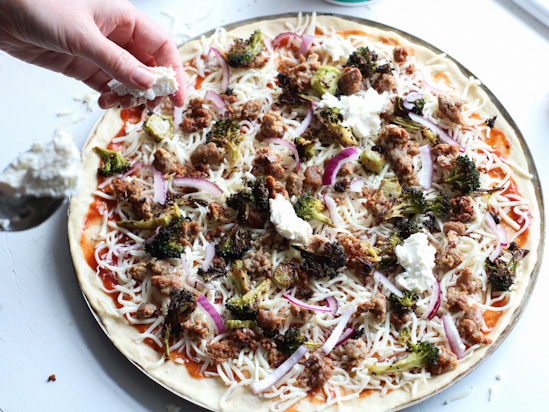 Adding dollops of ricotta cheese to an uncooked sausage broccoli pizza