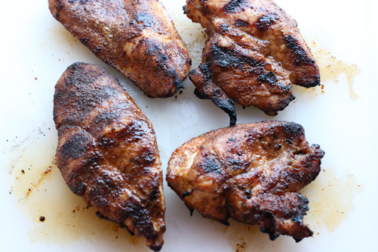Grilled, blackened chicken on a cutting board