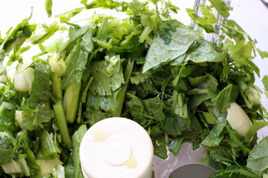 Ingredients for radish greens salsa in the bowl of a food processor