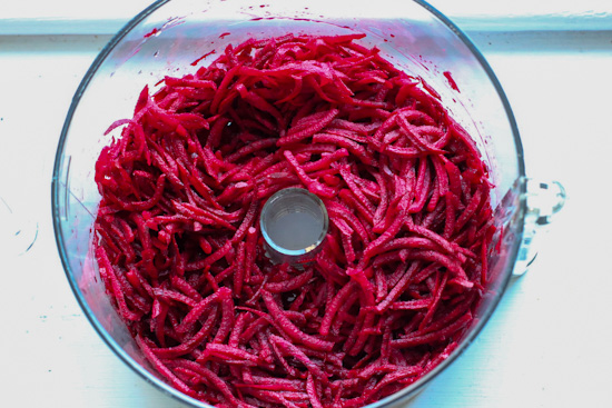 Shredded beets in the bowl of a food processor