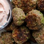 Beef and Arugula Meatballs on a platter with a side of harissa-yogurt sauce