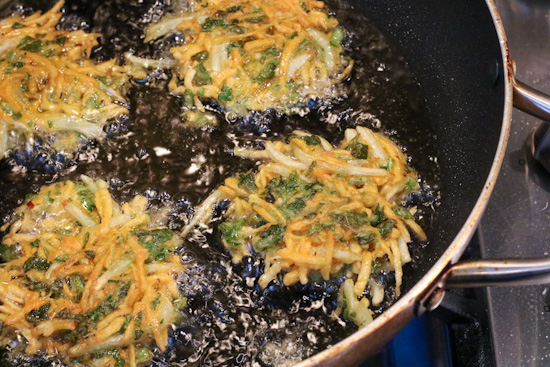 Batter for Sweet Potato Collard Green Fritters frying in a skillet