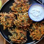 Batter for Sweet Potato Collard Green Fritters on a plate with dipping sauce
