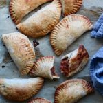 Squash and Country Ham Hand Pies on a sheet of parchment with a towel