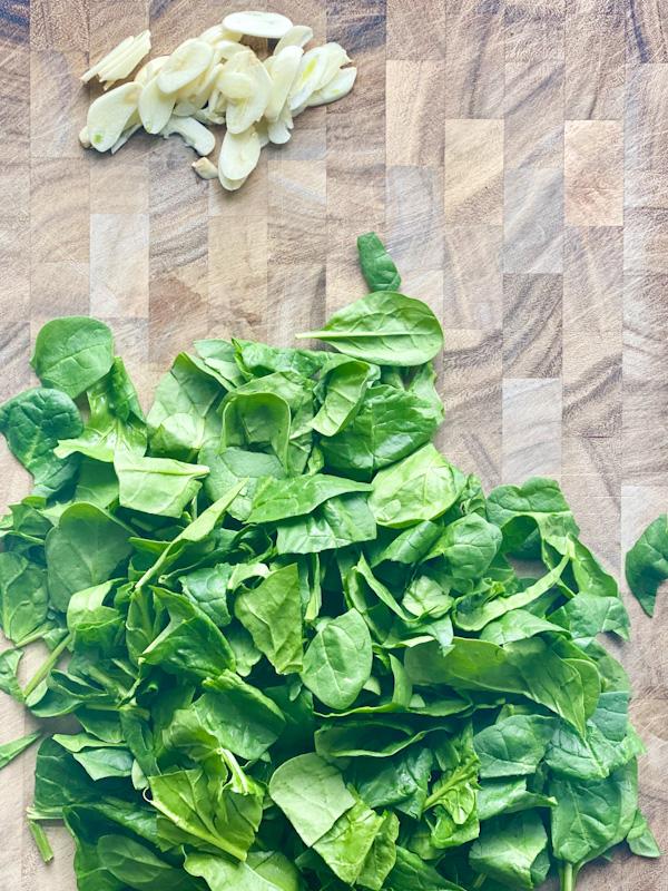 garlic and spinach on cutting board