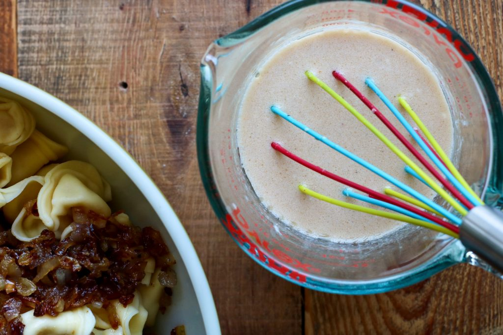 salad dressing in measuring cup with whisk